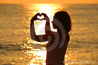 Woman makes heart by hands at sunset