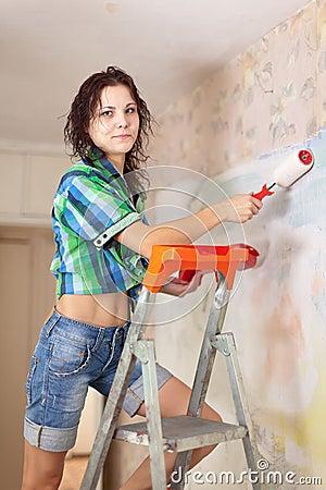 Woman makes repairs in  apartment