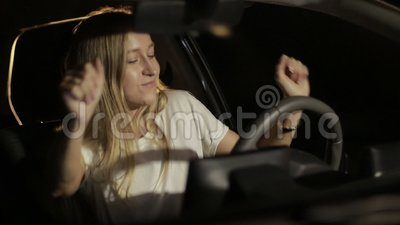 Woman making dance moves at night in car. Positive female driver sitting in modern car listening to music and making dancing moves while enjoying leisure at stock video footage