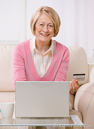 Woman making online purchase on laptop wit