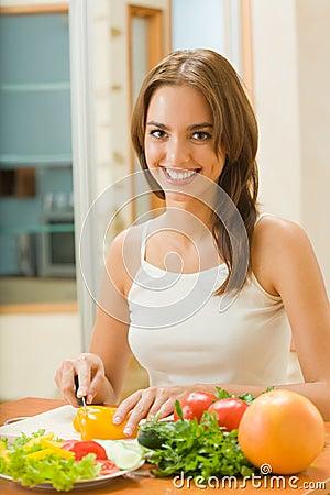 Woman making salad at kitchen
