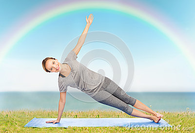 woman making yoga in side plank pose on mat stock photo