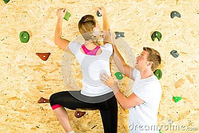 Woman and man climbing at climbing wall