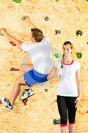 Woman and man climbing at climbing wall