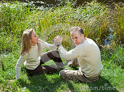The woman and the man for fun fight on a grass