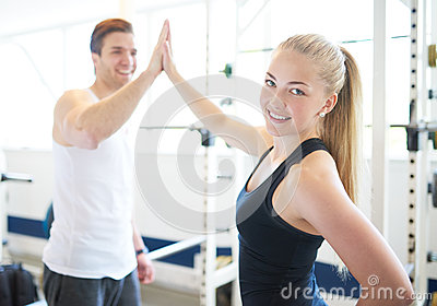 Woman and Man in Gym Celebrating with High Five Stock Photo