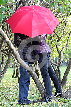 Woman and man hide behind red umbrella in park