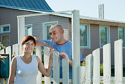 Woman and man near fence wicket