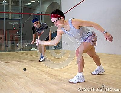 Woman and man playing squash