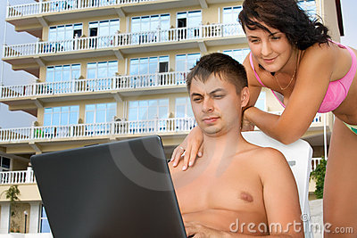 Woman and man reclining on chaise lounges on beach