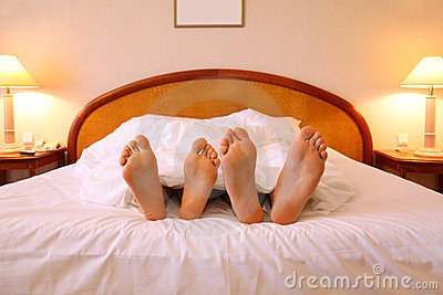 Woman and man rest on soft big bed