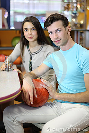 Woman and man sit at table in bowling