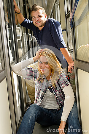 Woman and man sitting on train hall