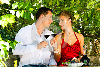 Woman and man sitting under grapevine and drinking
