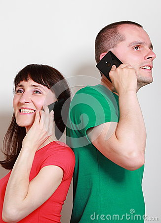 Woman and man with smile talking on mobile phone