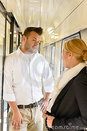 Woman and man talking on train hall