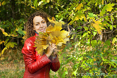 Woman with maple leaves in hands in wood in autumn