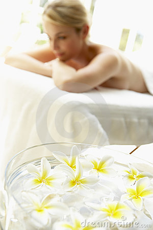 Woman On Massage Table With Flowers In Foreground