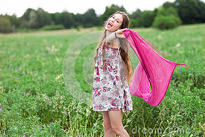 Woman in meadow holding scarf