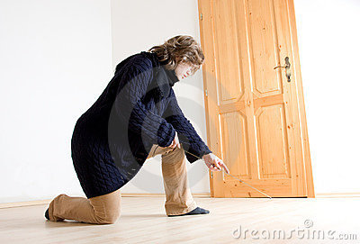 A woman measuring her floor