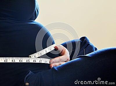 Woman measuring her waist size