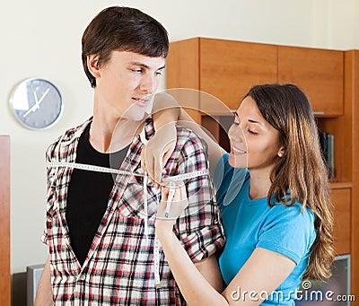 Woman measuring  shoulders  of boyfriend