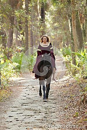 Woman in medieval dress riding horseback