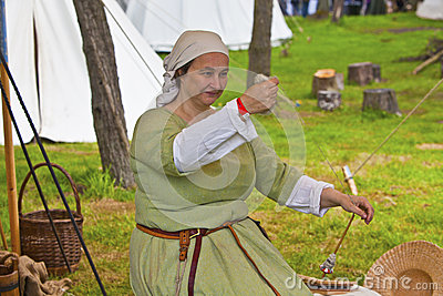 Woman in medieval setting and costume spinning yarn. Editorial Photo