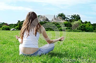 Woman meditates on green lawn