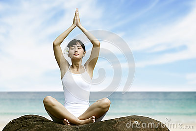 Woman meditating at beach