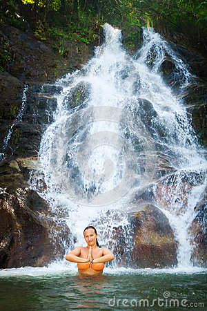 Woman meditating in beautiful waterfall