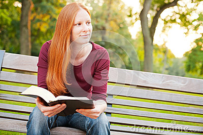 A Woman Meditating on the Bible in a Park