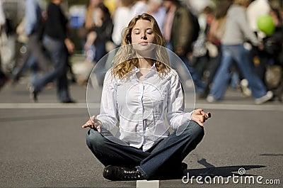 Woman meditating in busy urban street