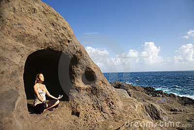 Woman meditating in cave.