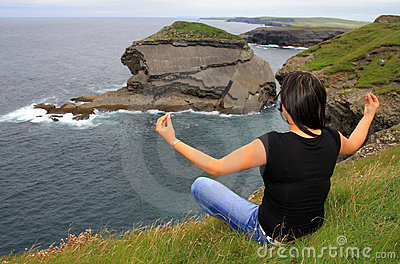 Woman meditating on irish cliffs