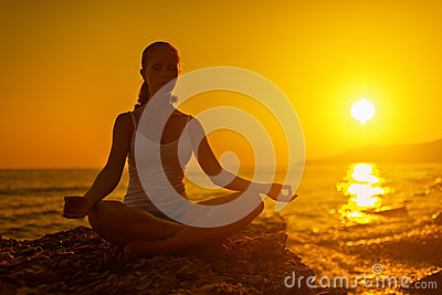 woman meditating in lotus pose at sunset stock photo