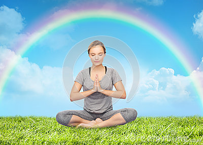 woman meditating in lotus yoga pose over rainbow stock