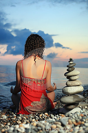 Woman meditating near to pyramid from pebble