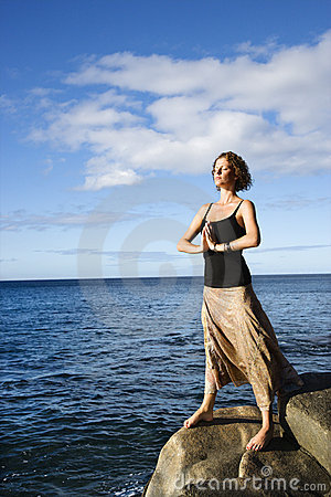 Woman meditating by ocean.