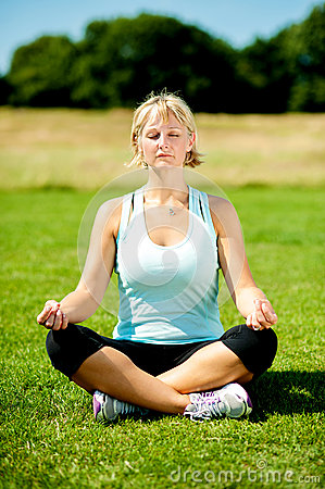 Woman meditating outdoors on a sunny day