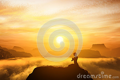 Woman meditating in sitting yoga position on the top of a mountains Stock Photo