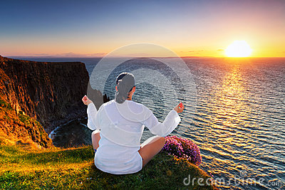 Woman at meditation on cliff