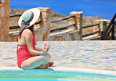 Woman meditation near the pool