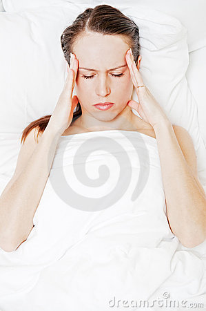 Woman with migraine lying in the bed