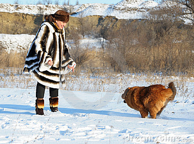 The woman in a mink fur coat plays with a dog