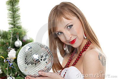 Woman with mirrored ball  near christmas tree.