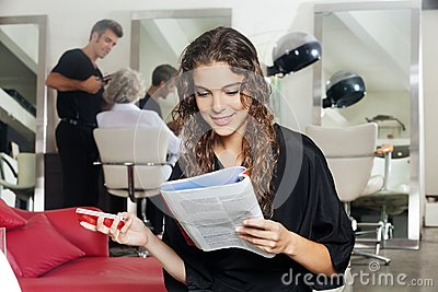 Woman with mobile phone reading magazine at hair royalty for Reading beauty salon