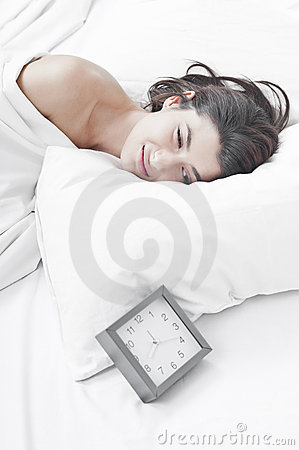 Woman in the morning looking at a clock