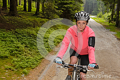 Woman mountain biking through forest road Stock Photo