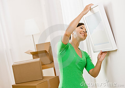 Woman moving into new home hanging picture